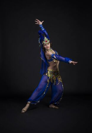 Young,smiling girl dancing the Eastern dance.Belly dance stage performance. Shooting in Studio on a dark background.