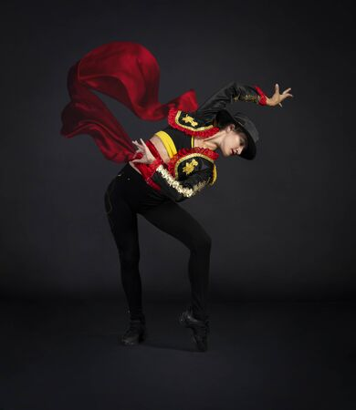 Plastic girl gracefully dancing in a stage costume stylized as a bullfighter. Studio shooting on a dark background.