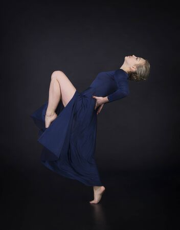 A girl in a blue dress with light hair is dancing a modern ballet. Studio shooting on a dark background.
