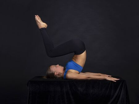 A slender girl performs yoga exercises. Studio shooting on a dark background.