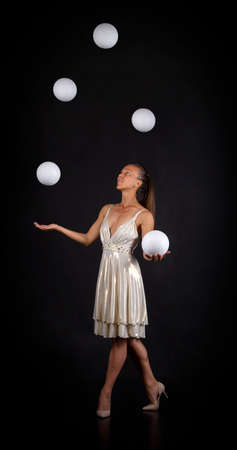A young woman in a white dress juggles balls on a dark background. 写真素材