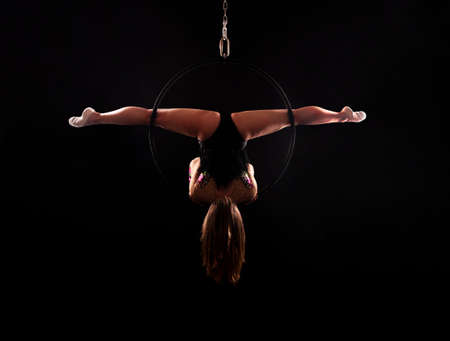 A young woman doing aerial acrobatics in a dark suit performs exercises in an aerial ring under contour lighting. Studio shooting on a dark background.