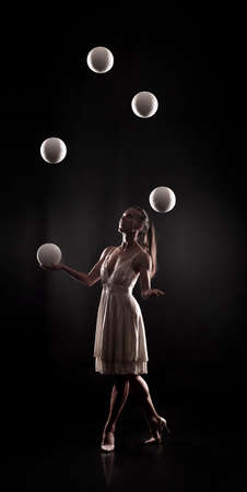 A young woman in a white dress is juggling balls on a dark background in a contoured light.Studio shooting. Banque d'images