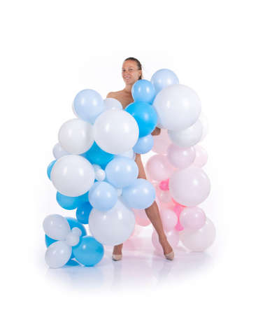 Nude girl with balloons posing on a white background. Studio shooting on a white background.