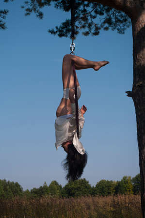 A girl in a white stage costume performs exercises in an aerial ring in the open air, against the background of the forest and the sky. Photography on the street.