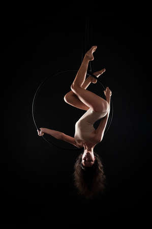 A young woman with long hair is engaged in aerial acrobatics in a beige bodysuit, performs exercises in an air ring shooting in a contour light. Studio shooting on a dark background.