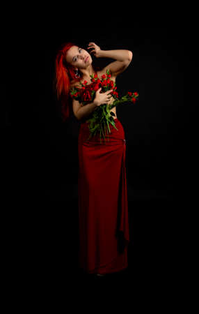 A girl with red hair, Topless, in a red skirt with a bouquet of flowers poses on a dark background. Studio shooting.