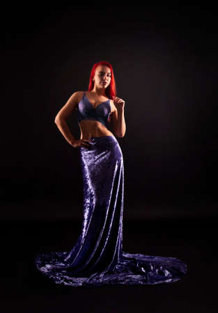 A girl with red hair, in a long lilac skirt, poses against a dark background in a contoured light. Studio shooting.