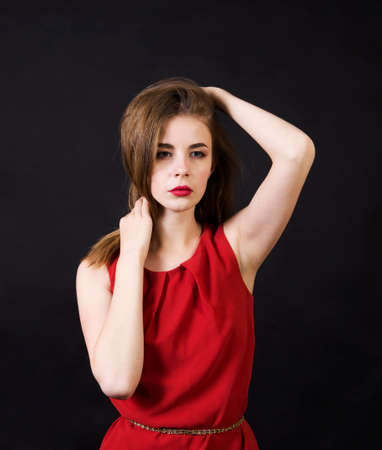 A beautiful girl in a red dress with long hair and a make-up. Studio shooting on a dark background, isolated image. Banque d'images