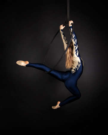 Slender girl-aerial acrobat in a blue and white suit with long hair, performs exercises in the air ring. Studio shooting on a dark background.