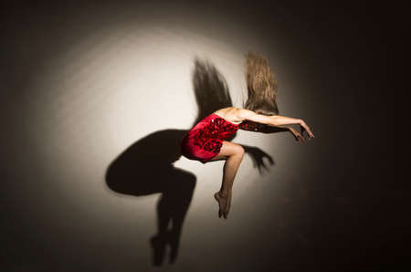 A girl in a red dress performs gymnastic jumps, a shadow from a figure appears on a white background. Studio photography.