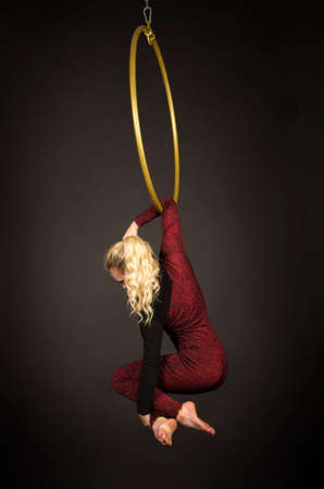 A slender blonde girl-an air acrobat in a red suit with long hair, performs exercises in an air ring. Studio shooting on a dark background.