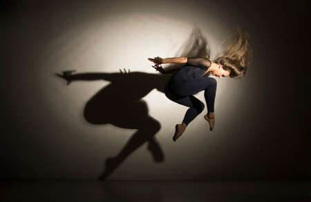 Girl in dark performs gymnastic jumping, on a white background there is a shadow from a shape. Studio photography.