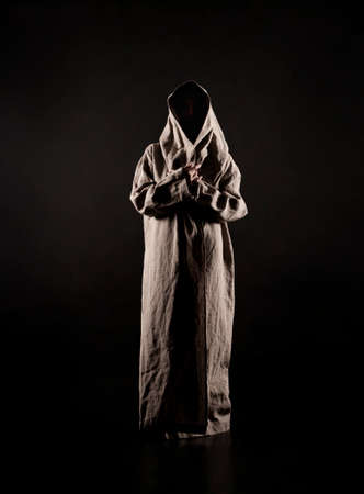 A young woman in a raincoat of coarse cloth on her naked body is isolated on a black background. Studio photography. Banque d'images