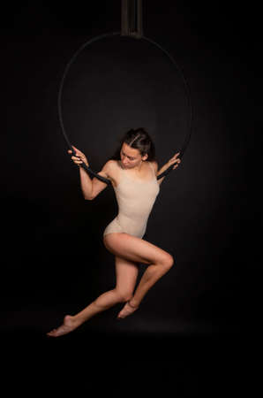 A young woman with long hair is engaged in aerial acrobatics in a beige bodysuit, performs exercises in the air ring. Studio shooting on a dark background.
