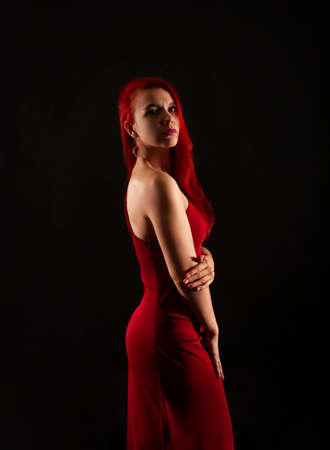 A girl with red hair, in a red dress posing on a dark background. Studio shooting.