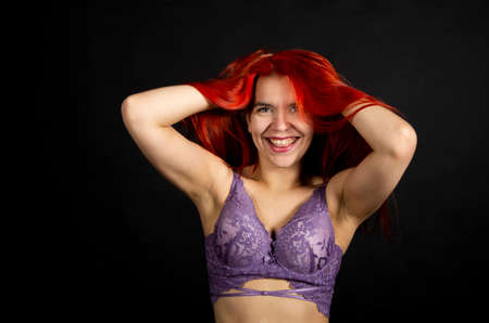 Portrait of a young, emotional woman in underwear on a dark background. Studio shooting.