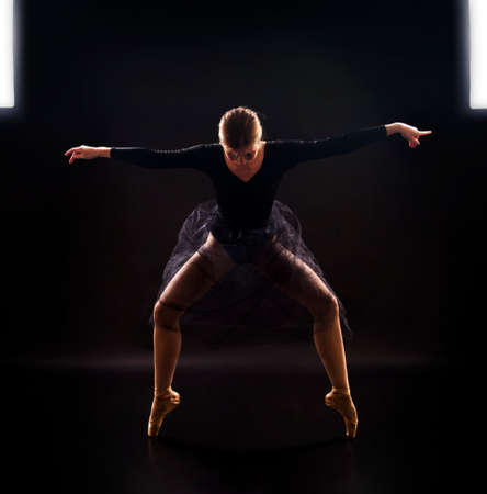 Charming girl ballerina in a black suit, is dancing a ballet in the light of the contour. Shooting a performance on a dark background.