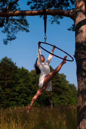 A girl in a white stage costume performs exercises in an aerial ring at the outdoor
