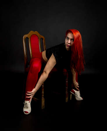 A young woman in red leggings and a black vest with long hair poses on a chair against a dark background. Studio shooting.