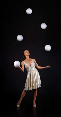 A young woman in a white dress juggles balls on a dark background. Banque d'images