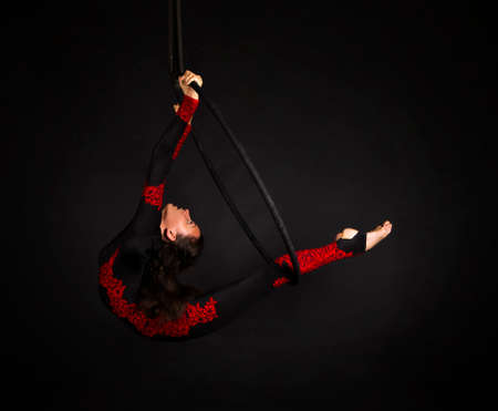 A young woman with long hair doing aerial acrobatics in a black and red suit, performs exercises in the air ring. Studio shooting on a dark background. Banque d'images - 160530348