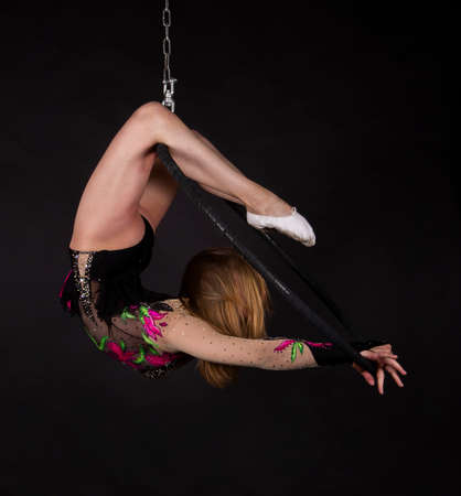 A young woman doing aerial acrobatics in a dark suit performs exercises in an aerial ring on a dark background. Studio shooting. Banque d'images