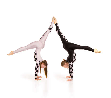 Two young female equilibrists perform acrobatic elements on a white background. Studio shooting. Banque d'images - 163984198