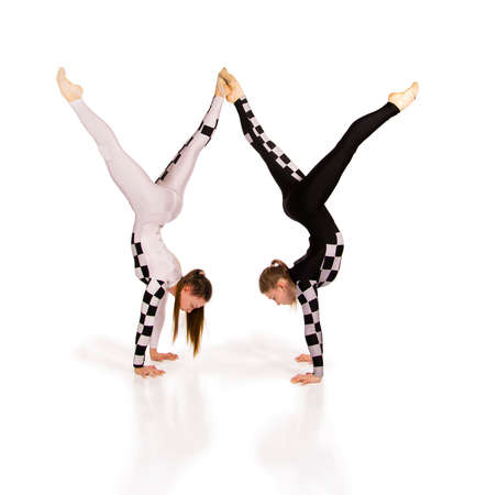 Two young female equilibrists perform acrobatic elements on a white background. Studio shooting.