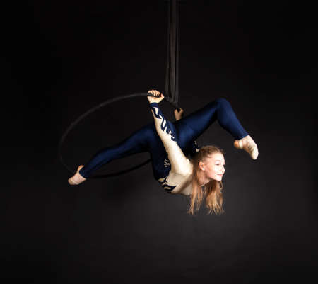 Slender girl - aerial acrobat in a blue and white suit with long hair, performs exercises in the air ring. Studio shooting on a dark background.