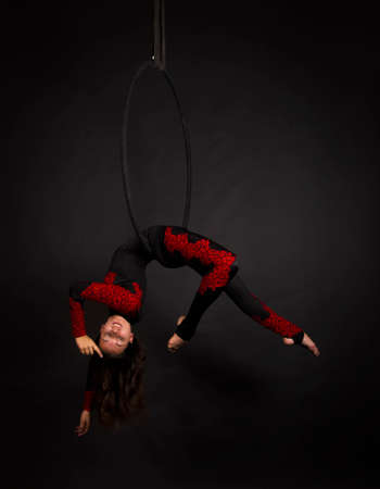A young woman with long hair doing aerial acrobatics in a black and red suit, performs exercises in the air ring. Studio shooting on a dark background.
