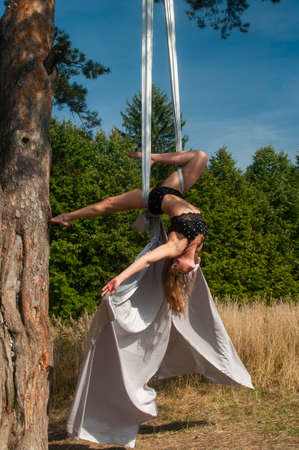 A slender girl with blonde hair, in a black stage costume, performs gymnastic and circus exercises on white silk against the background of the forest and the sky. Shooting on the street.