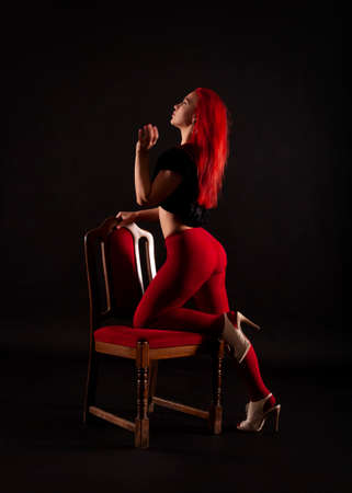 A girl with red hair, wearing red leggings poses on a chair on a dark background. Studio shooting. Banque d'images