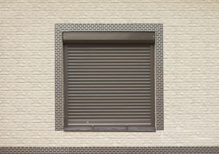 roller shutters: A window with brown Rolling Shutters. Wall decoration with artificial stone