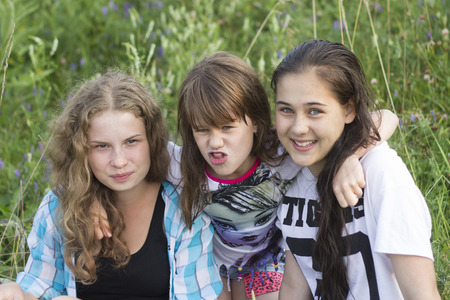 naughty girl: Three sisters girls hug each other and smile merrily in the grass. Smart, beautiful and naughty girl
