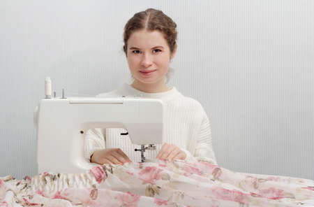 Dressmaker woman working with sewing machine.
