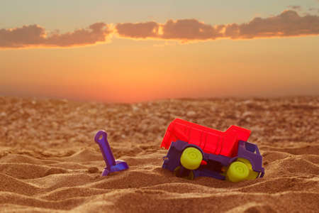Concept. A toy car and a scoop are in the sand against the background of a beautiful sunset in the Dakar desert.