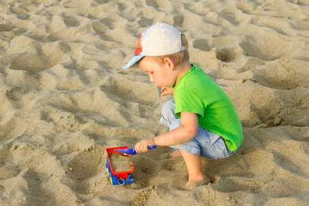 A toddler plays with a toy truck and a dustpan in the sand