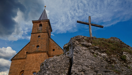 whitsun: View on a church and a cross on a rock in front of a wonderful clouded sky