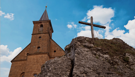 whitsun: View on a church and a cross on a rock in front of a wonderful clouded sky - This is the church Guegel, Schesslitz, Germany Stock Photo