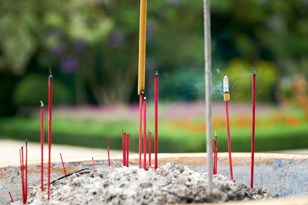 Burning red incense sticks infront of a buddhist temple with blurred flowers in the background