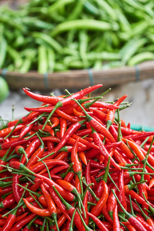 healthful: Fresh red chili peppers close up with green peppers in the background blured.