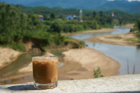 Iced coffee or caffe latte in front of a nice blurred landscape in Vietnam, Phong NhaKe Bang Nationalpark