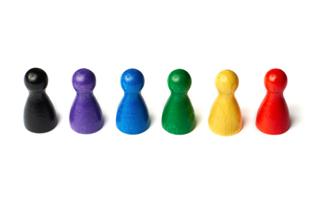 Colorful game figures standing in a row. Concept teamwork, diversity or rainbow colors Stockfoto