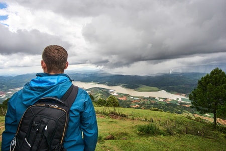 Young man standing on the mountain lang biang in Da-lat, Vietnam. Dramatic sky before the rain starts