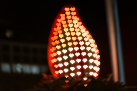 Silhouette of a fire with lights shaped as hearts, everything blurred. With copyspace.