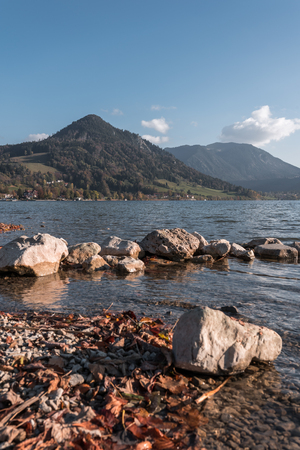 The Schliersee in autumn colors in the Bavarian mountains. With autumn leaves in the foreground.