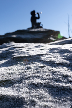 Woman on mountain top is taking a break and drinking water. Ice crystalls in the foreground.