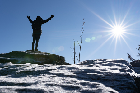 Cheering woman hiker open arms at mountain peak backlit with heavy lensflare and ice crystalls in the foreground.