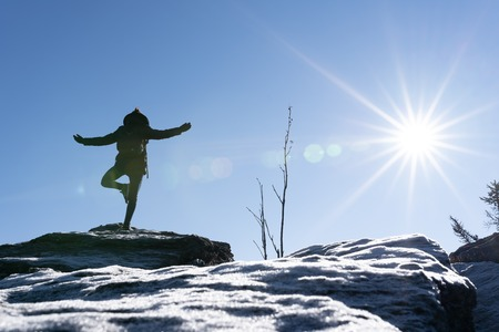 Young woman is doing yoga on a mountain peak with ice in the foreground. Bavarian forest, osser, germany. Standard-Bild